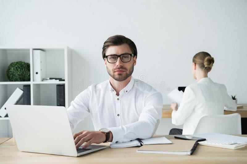 homem de negócios novo considerável que trabalha com o portátil no escritório moderno com assento do colega imagem de stock royalty free