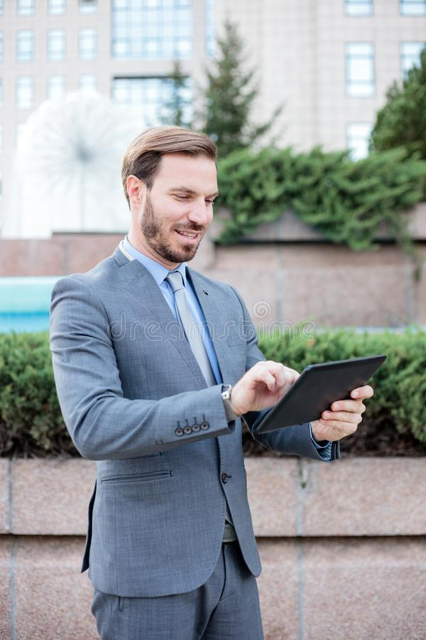 Homem de negócios novo, considerável que trabalha em uma tabuleta na frente de um prédio de escritórios imagem de stock