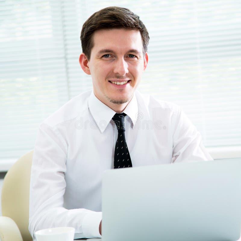 Homem de negócios novo considerável que trabalha no portátil foto de stock
