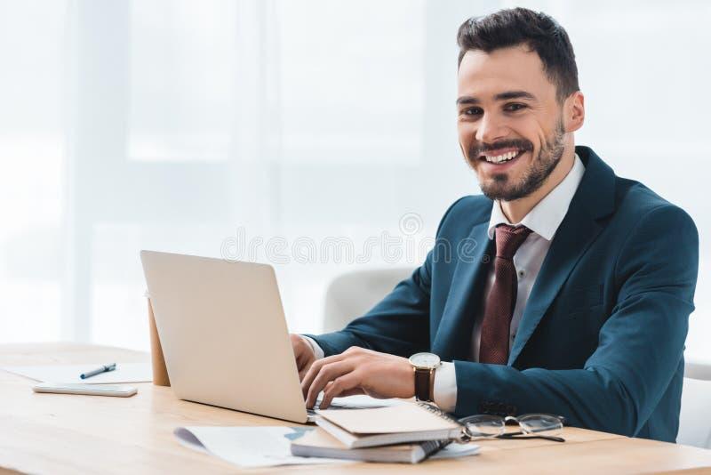 homem de negócios novo considerável que usa o portátil e sorrindo na câmera fotos de stock royalty free