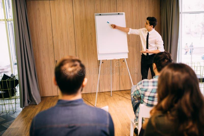 Homem de negócios novo considerável seguro que dá a apresentação usando o flipchart no escritório foto de stock royalty free