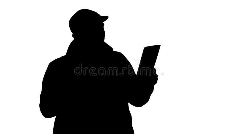 Homem de negócios novo da silhueta que usa a tabuleta digital que faz a chamada video fotografia de stock royalty free