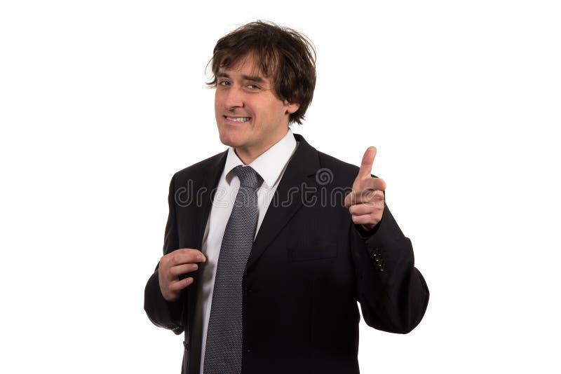 Homem de negócios novo de sorriso com seus gestos de mão que imita a arma aguçado em linha reta à câmera imagem de stock royalty free