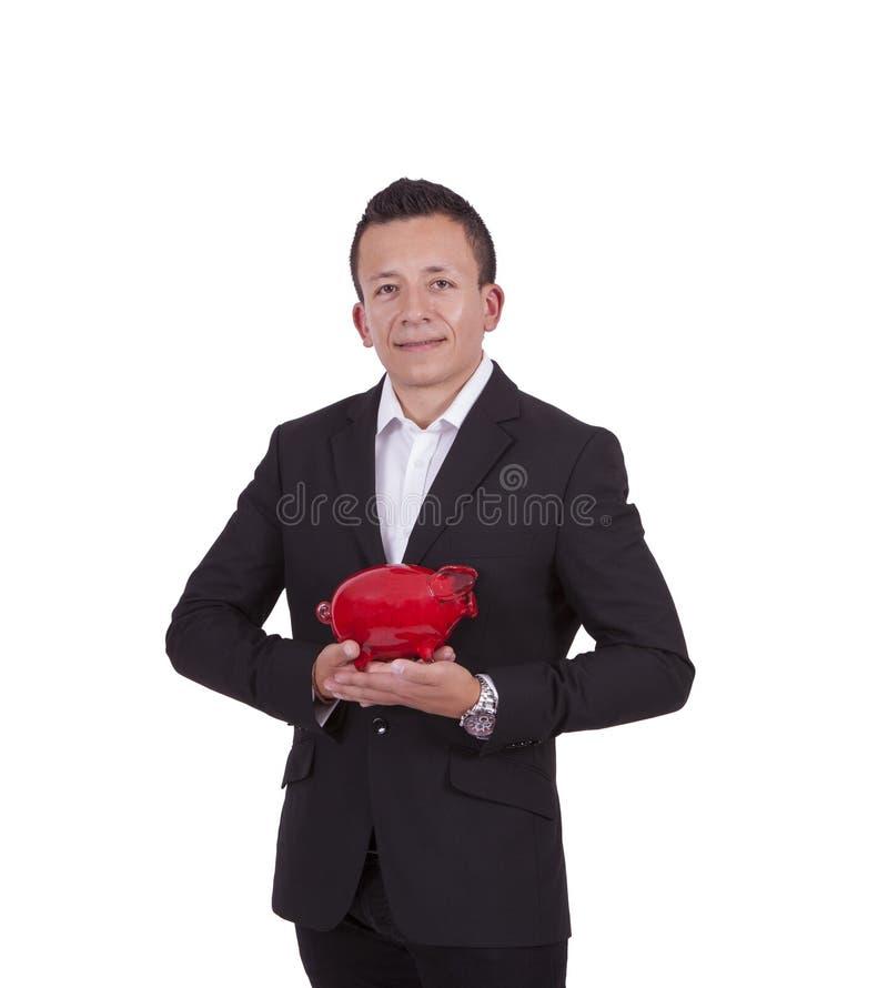 Homem de negócios novo de sorriso que levanta com um mealheiro imagem de stock