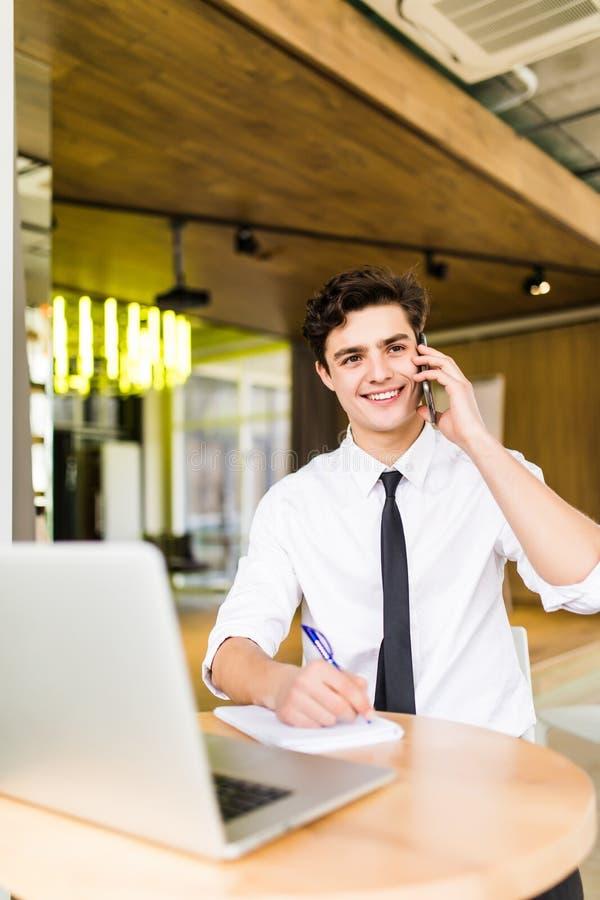 Homem de negócios novo de sorriso que senta-se atrás de sua mesa com portátil e que fala no telefone celular no escritório foto de stock