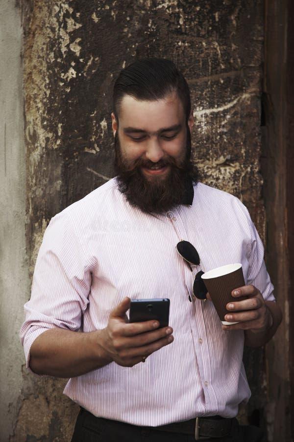 Homem de negócios novo do moderno com a barba que guarda o telefone e um café foto de stock royalty free