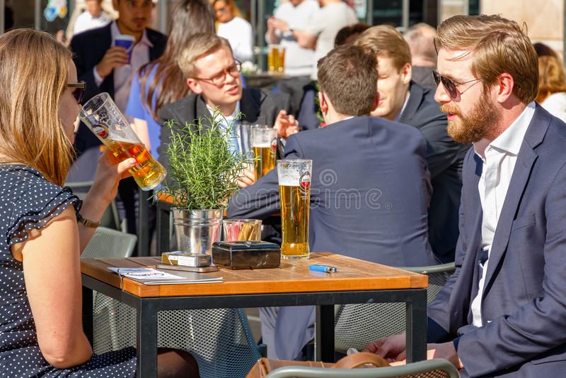 Homem de negócios novo e mulheres de negócios que bebem em uma barra exterior embalada foto de stock royalty free