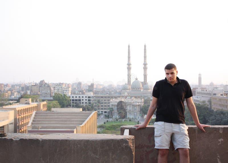 Homem de negócios novo egípcio árabe com mesquita e igreja imagem de stock