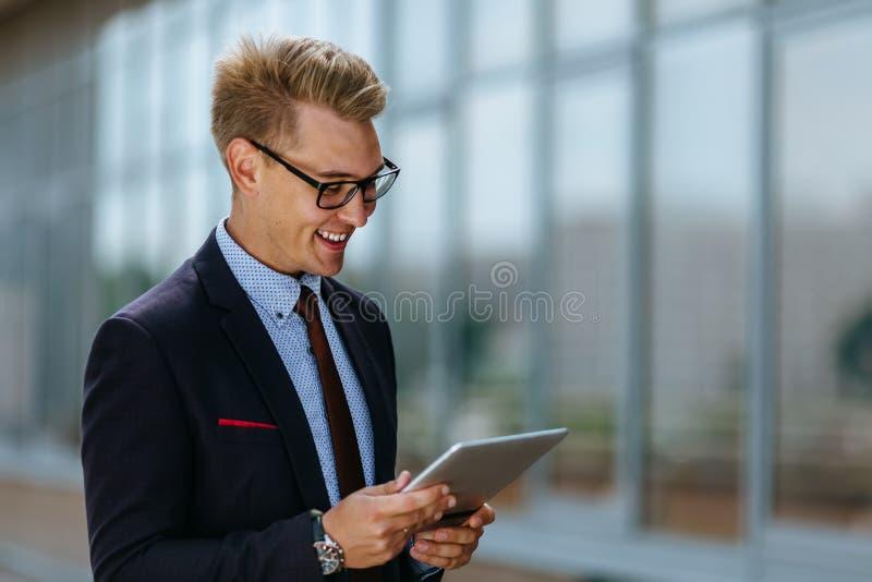 Homem de negócios novo elegante que usa sua tabuleta do PC Retrato de um gerente executivo masculino na roupa na moda com PC da t fotos de stock