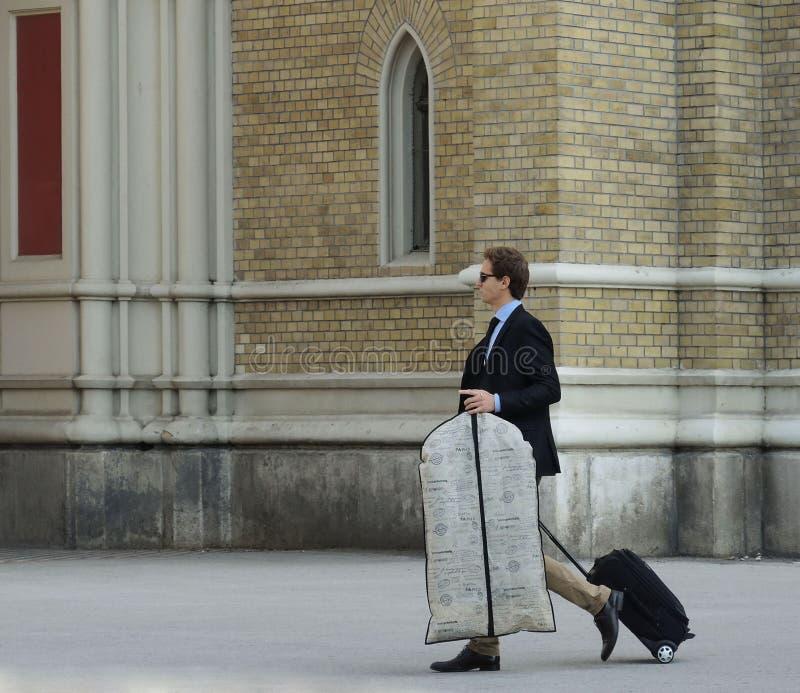 Homem de negócios novo em um terno e laço com mala de viagem rodada imagens de stock royalty free
