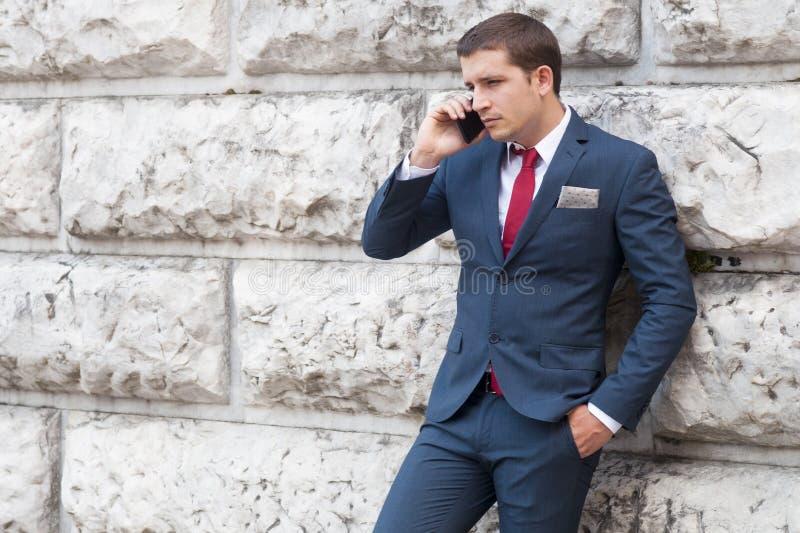 Homem de negócios novo em um terno e em um laço que fala smartphone AG foto de stock