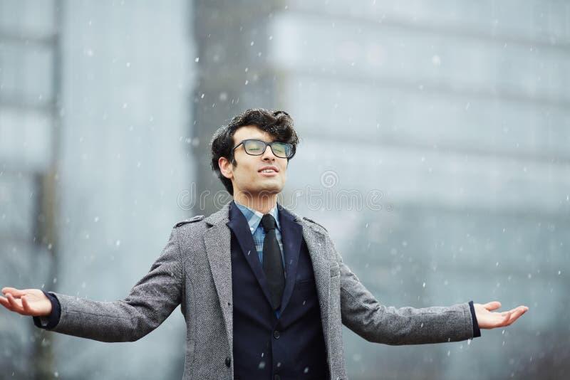 Homem de negócios novo Enjoying First Snow foto de stock
