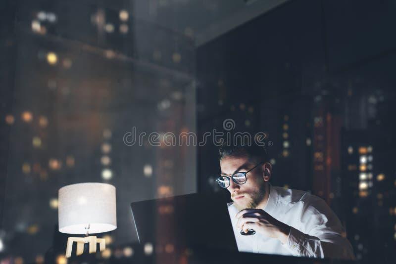 Homem de negócios novo farpado que trabalha no escritório moderno do sótão na noite Equipe usando a mensagem texting do caderno c foto de stock royalty free