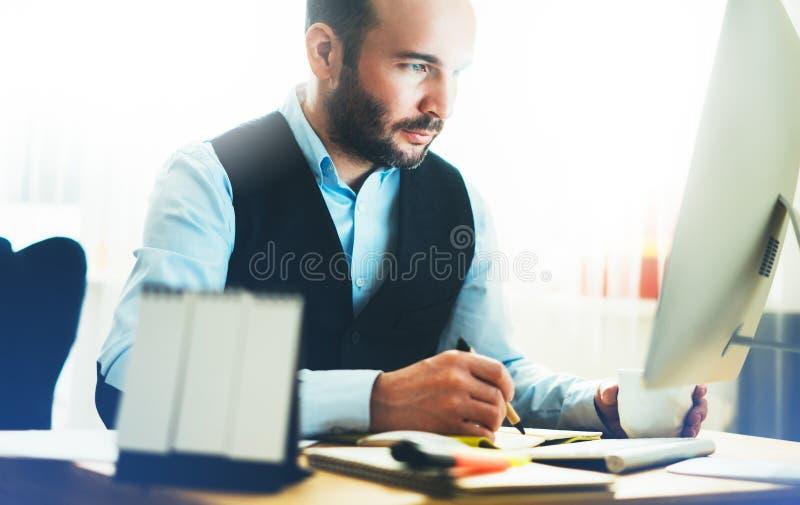 Homem de negócios novo farpado que trabalha no escritório moderno Vista de pensamento do homem do consultante no computador do mo fotos de stock