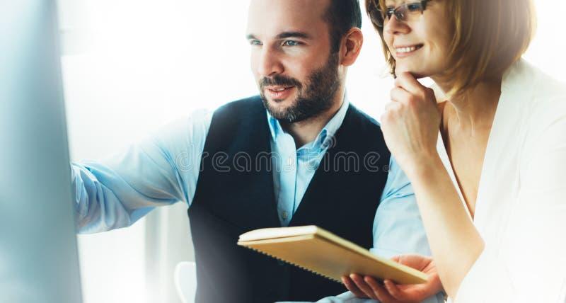 Homem de negócios novo farpado que trabalha no escritório Vista de pensamento do homem do diretor no computador do monitor Encont fotos de stock royalty free
