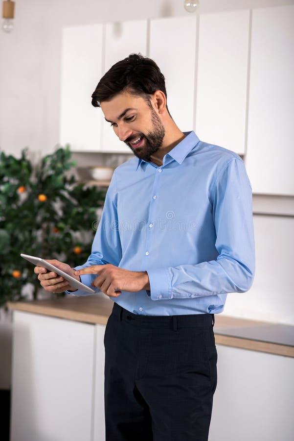 Homem de negócios novo farpado que usa sua tabuleta fotos de stock royalty free