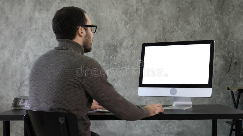 Homem de negócios novo farpado que woking no computador Indicador branco imagens de stock royalty free