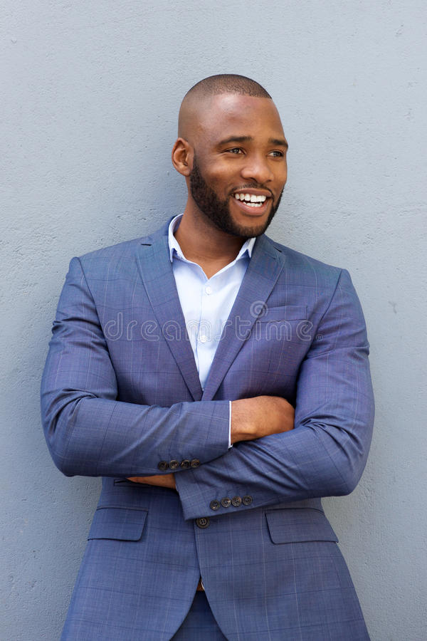Homem de negócios novo feliz que inclina-se contra a parede com seus braços cruzados fotografia de stock royalty free