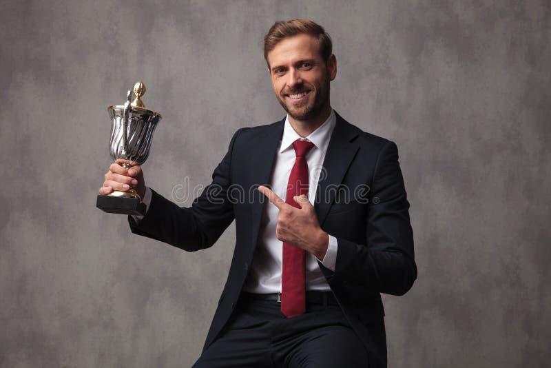 Homem de negócios novo feliz que poiting a seus troféu e sorrisos imagem de stock royalty free