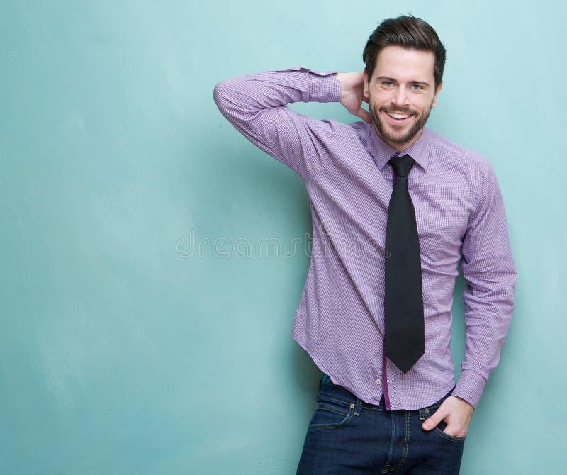 Homem de negócios novo feliz que sorri contra o fundo azul fotografia de stock royalty free