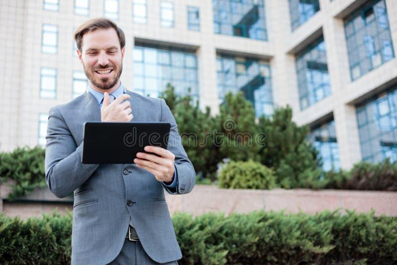 Homem de negócios novo feliz que trabalha em uma tabuleta na frente de um prédio de escritórios fotos de stock royalty free