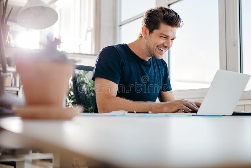 Homem de negócios novo feliz que usa o portátil em sua mesa de escritório fotos de stock royalty free
