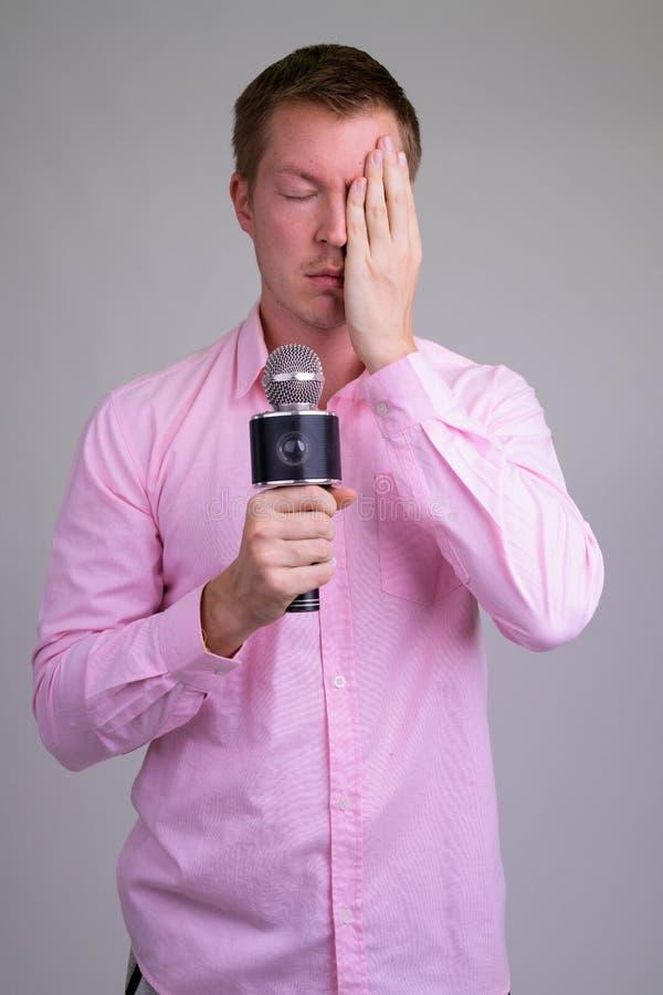 Homem de negócios novo forçado como a cara da coberta do anfitrião e vista frustrado imagens de stock