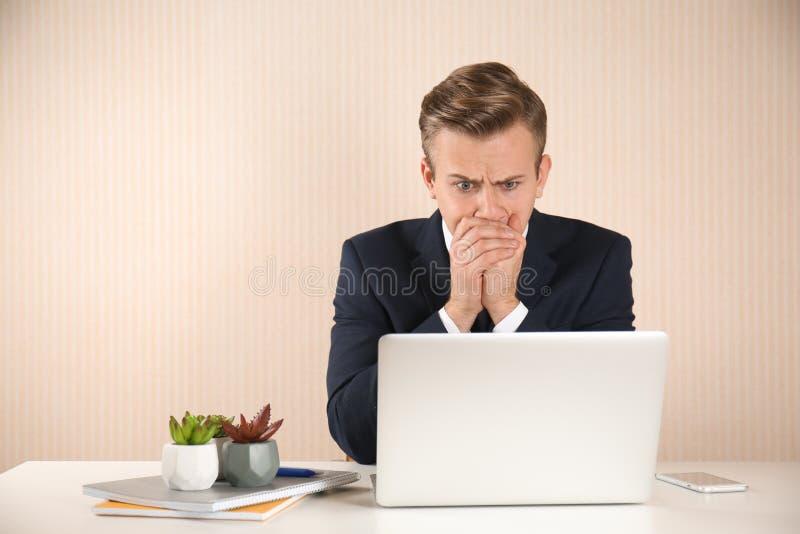 Homem de negócios novo forçado na tabela no fundo claro imagens de stock