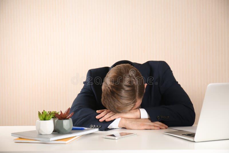 Homem de negócios novo forçado na tabela no fundo claro fotos de stock