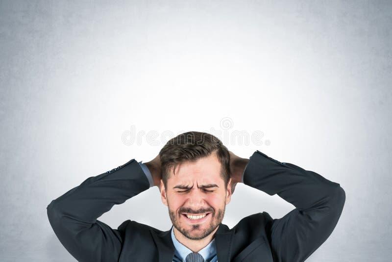 Homem de negócios novo forçado, parede cinzenta imagens de stock