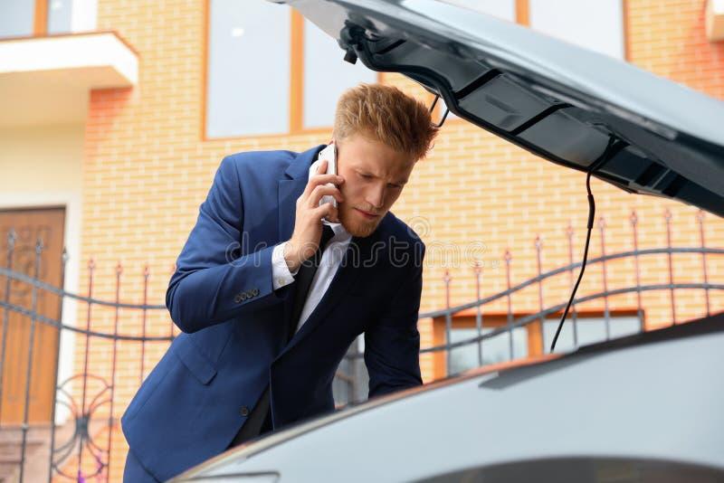 Homem de negócios novo incomodado que fala no telefone perto de carro quebrado imagem de stock royalty free