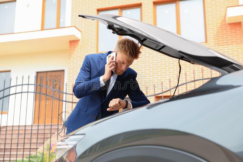 Homem de negócios novo incomodado que fala no telefone perto de carro quebrado fotos de stock royalty free
