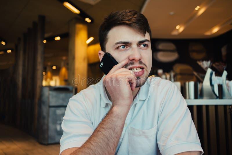 Homem de negócios novo irritado que fala no telefone ao sentar-se em um restaurante fino fotos de stock royalty free