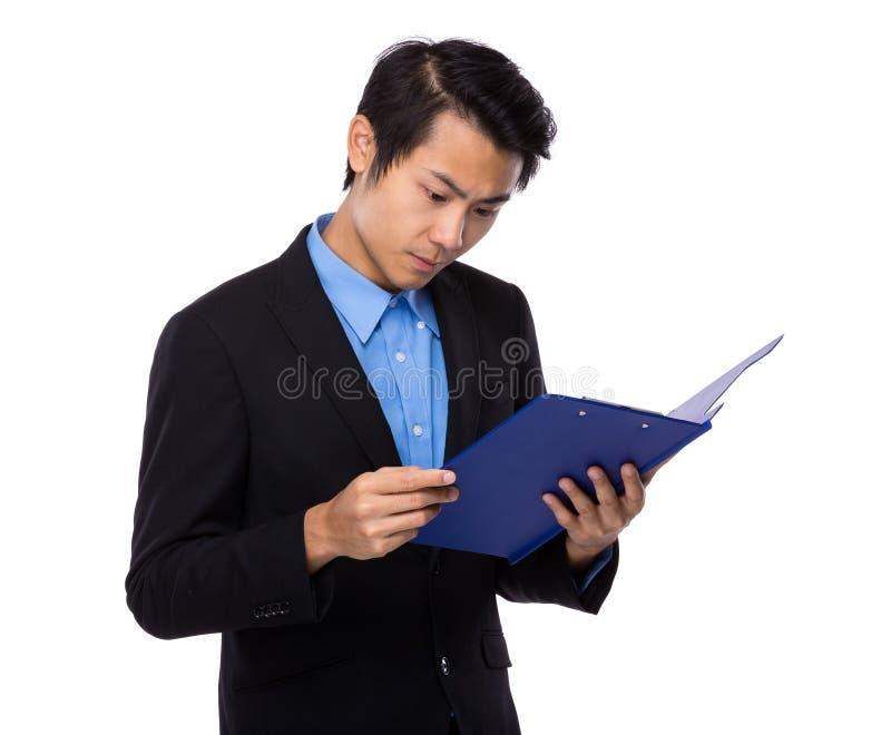 Homem de negócios novo lido na prancheta foto de stock royalty free