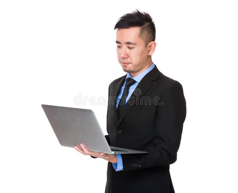 Homem de negócios novo lido no laptop fotos de stock royalty free