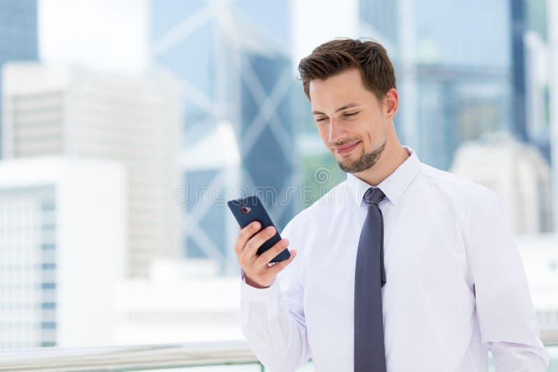 Homem de negócios novo lido no telefone celular foto de stock