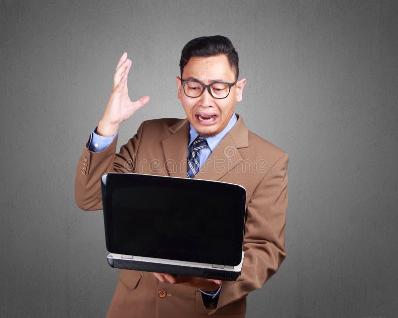Homem de negócios novo Looking em Expressi do portátil, chocado e o assustado fotos de stock