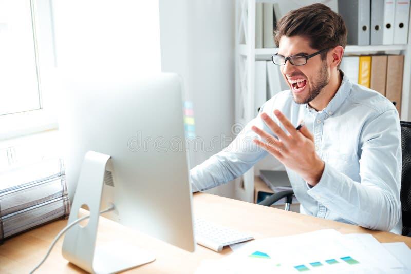 Homem de negócios novo louco irritado que trabalha com computador e gritaria fotos de stock royalty free