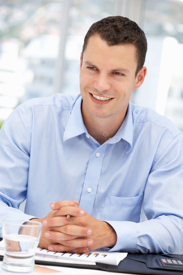 Homem de negócios novo na mesa fotografia de stock