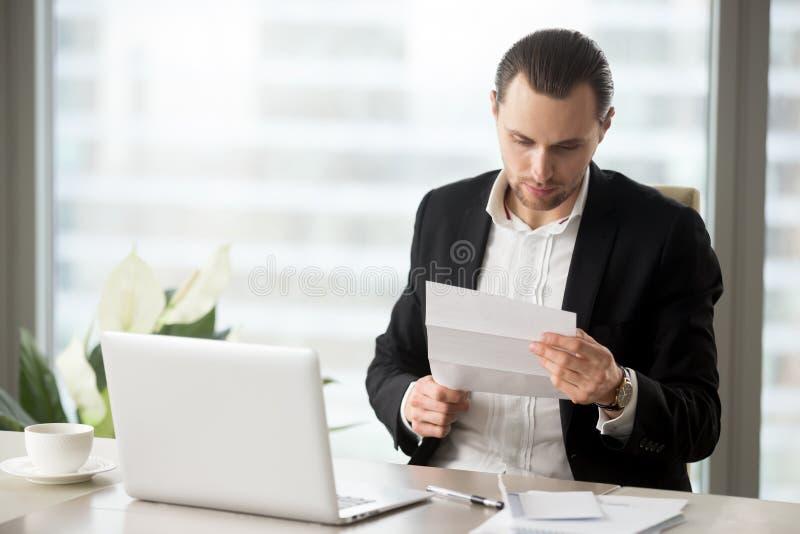 Homem de negócios novo no escritório que lê o lett financeiro importante foto de stock royalty free