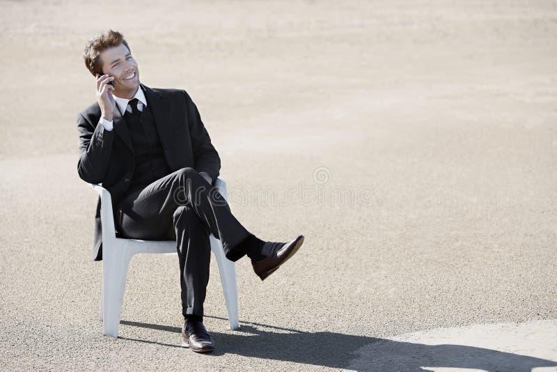 Homem de negócios novo no telefone no deserto fotografia de stock royalty free