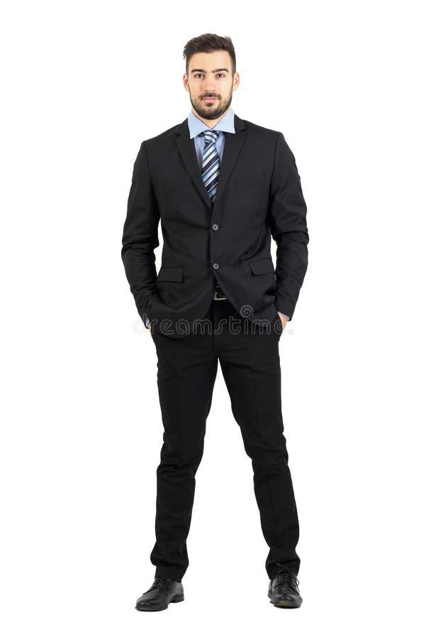Homem de negócios novo no terno com mãos em uns bolsos que olham a câmera fotos de stock
