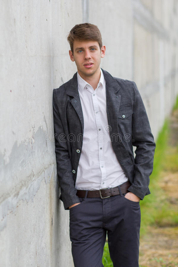 Homem de negócios novo no terno que inclina-se na parede imagem de stock royalty free
