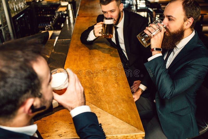 Homem de negócios novo no urso da bebida do terno na barra Sentam-se na frente de se imagens de stock