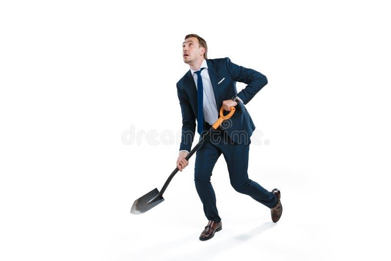 Homem de negócios novo no vestuário formal que escava com pá e que olha acima fotografia de stock