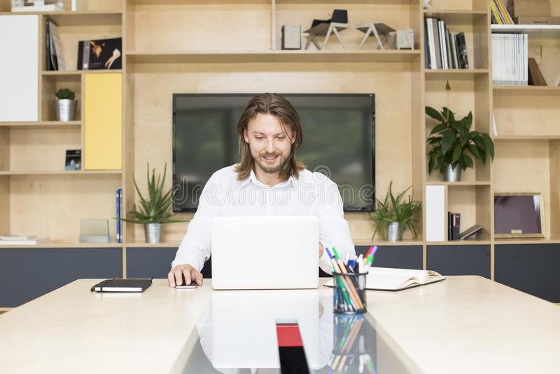 Homem de negócios novo ocasionalmente vestido que trabalha em um portátil quando se sente imagem de stock royalty free