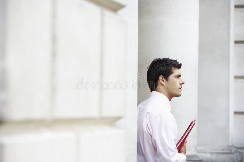 Homem de negócios novo pensativo Holding File fotografia de stock