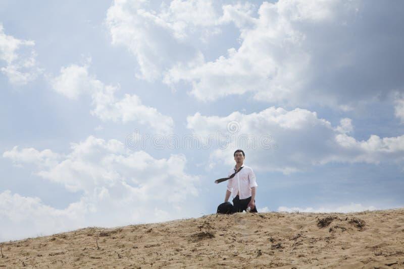 Homem de negócios novo perdido e que anda através do deserto, distante fotos de stock