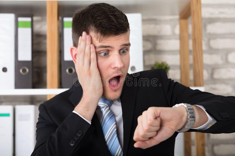 Homem de negócios novo preocupado Checking Time In o seu relógio imagens de stock royalty free