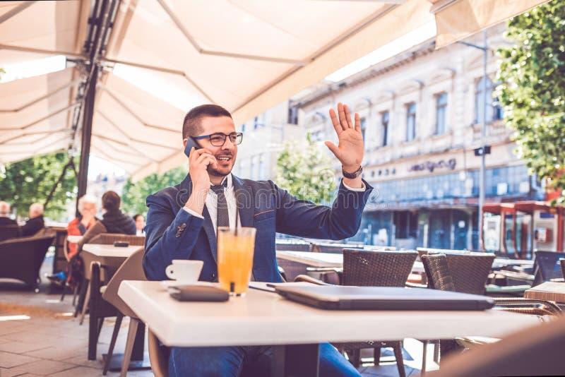 Homem de negócios novo que acena a alguém ao falar no telefone durante a ruptura de café em um café imagens de stock